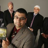 Photo - Adam Soltani, foreground, with the Council on American-Islamic Relations Oklahoma Chapter, shows a copy of a free DVD his organization is giving away to non-Muslims interested in learning about the life of the Prophet Muhammad. Others pictured are, from left, Sheryl Siddiqui, Jenell Mapp-Maynard, Imad Enchassi and Saad Mohammed.  Photo by Doug Hoke,  The Oklahoman