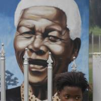 Photo - A child stands in front of a portrait of former president Nelson Mandela in a Park in Soweto, South Africa, Thursday, March, 28, 2013. 94-year-old Mandela, the anti-apartheid leader who became South Africa's first black president, has been hit by a lung infection again and is in a hospital, the presidency said. Mandela, has become increasingly frail in recent years and has been hospitalized several times in recent months, including earlier this month when he underwent what authorities said was a scheduled medical test. The Nobel laureate is a revered figure in South Africa, which has honored his legacy of reconciliation by naming buildings and other places after him and printing his image on national banknotes. (AP Photo/Denis Farrell)