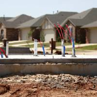 Photo - Foundation work on a home under construction is seen with a line of completed homes in the background along NW 182 Terrace in The Grove addition in northwest Oklahoma City.  BRYAN TERRY - THE OKLAHOMAN