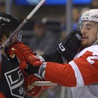 Photo - Los Angeles Kings center Colin Fraser, left, and Detroit Red Wings defenseman Brendan Smith rough each other during the second period of an NHL hockey game, Saturday, Jan. 11, 2014, in Los Angeles. (AP Photo/Mark J. Terrill)