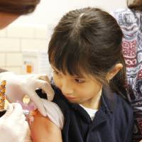 Photo - Kindergarten student Rosa Melendez, 6, gets flu shot Wednesday at Mark Twain Elementary. Photo by Paul B. Southerland, The Oklahoman  PAUL B. SOUTHERLAND