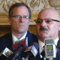 Photo - Elvin Daniel, right, whose sister Zina was killed by her husband last October at a Brookfield spa, said the tragedy could have been avoided if the law required background checks for private transactions of guns during a news conference with law enforcement officials and some Democratic lawmakers, including Rep. Jon Richards, left, Thursday, March 21, in Madison, Wis.  Democrats have a new proposal that would make it illegal to purchase or transfer guns without running background checks. (AP Photo/Kevin Wang)