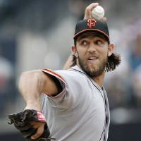 Photo - San Francisco Giants starting pitcher Madison Bumgarner delivers in the first inning of a baseball game against the New York Mets in New York, Sunday, Aug. 3, 2014. (AP Photo/Kathy Willens)