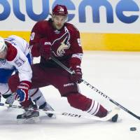 Photo - Phoenix Coyotes' Antoine Vermette, right, shoots in front of Montreal Canadiens' David Desharnais in the first period of an NHL hockey game on Thursday, March 6, 2014, in Glendale, Ariz. (AP Photo/The Arizona Republic, Patrick Breen) MARICOPA COUNTY OUT; NO SALES