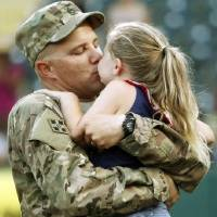 Photo - Staff sgt. Jason Bellar hugs his four-year-old daughter Alexis Bellar after returning home after a nine month tour in Afghanistan and surprising his kids during a minor league baseball game between the Oklahoma City Redhawks and the New Orleans Zephyrs at Chickasaw Bricktown Ballpark on July 8, 2014. Photo by KT King/The Oklahoman