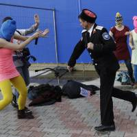 Photo - A Cossack militiaman attacks Nadezhda Tolokonnikova and a photographer as she and fellow members of the punk group Pussy Riot, including Maria Alekhina, right, in the pink balaclava, stage a protest performance in Sochi, Russia, on Wednesday, Feb. 19, 2014. The group had gathered in a downtown Sochi restaurant, about 30km (21miles) from where the Winter Olympics are being held. They ran out of the restaurant wearing brightly colored clothes and ski masks and were set upon by about a dozen Cossacks, who are used by police authorities in Russia to patrol the streets. (AP Photo/Morry Gash)