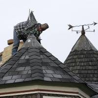 Photo - Walter Jacob stands on the peak of a roof Thursday, Feb. 7, 2013, in the Ocean Grove section of Neptune, N.J., as he works to seal the leak around a weather vane at a home damaged by Superstorm Sandy. The region is bracing for the threat of a snow storm in the next few days. (AP Photo/Mel Evans)