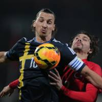 Photo - Turkey's Ersan Gulum, rear, vies with Sweden's Zlatan Ibrahimovic during their International Friendly soccer match at 19 Mayis Stadium in Ankara, Turkey, Wednesday, March 5, 2014.(AP Photo)
