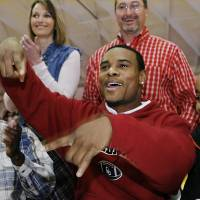 Photo - Dewar defensive back Ronnel Lewis flashes the upside down 'Horns gesture as he responds to loud applause from family, friends and student body who watched him sign letter of intent to play football at the University of Oklahoma during a school-wide assembly in the school's gym Wednesday morning, February 4, 2009.  BY JIM BECKEL, THE OKLAHOMAN