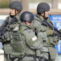 Photo - Corona, Calif., police officers stand near the site of a police shooting Thursday in Corona. Former Los Angeles police officer Christopher Dorner is suspected of shooting two LAPD officers who were sent to Corona to protect someone Dorner had threatened in a rambling online manifesto. AP PHOTO