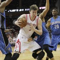 Photo - Houston Rockets center Omer Asik (3) grabs an offensive rebound away from Orlando Magic forward Tobias Harris, behind, during the second half of an NBA basketball game Monday, April 1, 2013 in Houston. Houston won 110-103. (AP Photo/Bob Levey)
