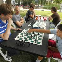 Photo -   Jake Williams, left, plays chess with Case Pirrong, 13, at the Myriad Gardens. Williams, a member of the OKC Challengers Chess Club, is organizing chess games open to the public each Saturday in August. Photo by Paul Hellstern, The Oklahoman   PAUL HELLSTERN -
