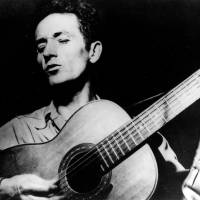 Photo - Iconic folk singer-songwriter Woody Guthrie, an Okemah native, sings a song and plays his guitar in this undated file photo.  (AP Photo)   - AP