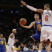 Photo - Golden State Warriors' Stephen Curry (30) drives past New York Knicks' Tyson Chandler (6) during the second half of an NBA basketball game on Friday, Feb. 28, 2014, in New York. (AP Photo/Frank Franklin II)
