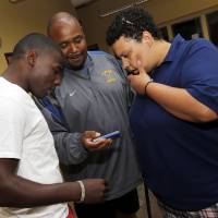 Photo - A. Jaye Johnson, middle, unit director at the Memorial Park club location, 3535 N. Western Ave., of the Boys & Girls Clubs of Oklahoma County, shows pictures of flooding at the club to Foster Riley, left, and Kris Minnis in Oklahoma City, Wednesday, July 2, 2014. The club is still recovering from a flood during a recent thunderstorm. Minnis, who formerly worked at the club, has raised Riley as her own son. Photo by Nate Billings, The Oklahoman
