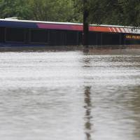 Photo - A San Antonio metro bus sits in floodwaters after it was swept off the road during heavy rains, Saturday, May 25, 2013, in San Antonio. (AP Photo/Eric Gay)