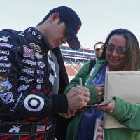Photo - Driver Kyle Larson (42) signs an autograph after qualifying for the NASCAR Nationwide series auto race at Bristol Motor Speedway on Saturday, March 15, 2014, in Bristol, Tenn. Larson will start from the pole position. (AP Photo/Wade Payne)