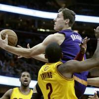 Photo - Phoenix Suns' Goran Dragic, from Slovenia, goes in for a shot against Cleveland Cavaliers' Kyrie Irving (2) in the first quarter of an NBA basketball game, Sunday, Jan. 26, 2014, in Cleveland. (AP Photo/Mark Duncan)