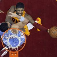 Photo - Cleveland Cavaliers' Kyrie Irving shoots over Denver Nuggets' JaVale McGee in the first quarter of an NBA basketball game Saturday, Feb. 9, 2013, in Cleveland. (AP Photo/Mark Duncan)