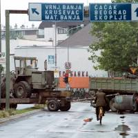 Photo - A biker rides past Yugoslav army vehicles and machinery blocking the road in downtown Kraljevo, some 160 km (100 miles) south of Belgrade Friday, June 25, 1999. Hundreds of Yugoslav army reservists continued a blockade of the roads in central Serbia, demanding their salaries and per diem for the three months of NATO attacks on Yugoslavia. (AP PHOTO / Mikica Petrovic) YUGOSLAVIA OUT COMMERCIAL ONLINE OUT 	ORG XMIT: 1001302112516572