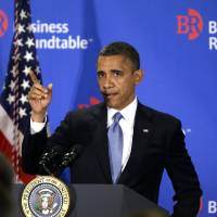 Photo - President Barack Obama gestures as he asks if the back of the room could hear him after the podium microphone stopped working while he was speaking about the fiscal cliff during an address before the Business Roundtable, an association of chief executive officers, Wednesday, Dec. 5, 2012, in Washington. (AP Photo/Charles Dharapak)