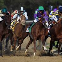 Photo - Victor Espinoza rides California Chrome around turn four to a victory during the 140th running of the Kentucky Derby horse race at Churchill Downs Saturday, May 3, 2014, in Louisville, Ky. (AP Photo/Matt Slocum)