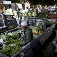 Photo - An Egyptian street vendor sits at the back of a pickup truck along with vegetables displayed for sale, in Cairo, Egypt, Thursday, Jan. 3, 2013. (AP Photo/Nasser Nasser)