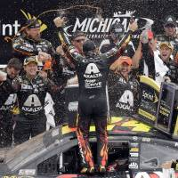Photo - Jeff Gordon celebrates his victory with his crew after the NASCAR Sprint Cup Series Pure Michigan 400 auto race at Michigan International Speedway in Brooklyn, Mich., Sunday, Aug. 17, 2014. (AP Photo/Paul Sancya)