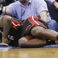 Photo - Miami Heat forward LeBron James grimaces as he lies on the floor with a bloody nose in the fourth quarter of an NBA basketball game against the Oklahoma City Thunder in Oklahoma City, Thursday, Feb. 20, 2014. James was struck by Thunder's Serge Ibaka on a drive to the basket. Miami won 103-81. (AP Photo/Sue Ogrocki)