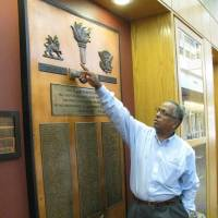 Photo - Mel Tewahade observes a display commemorating the service of OSU faculty to Ethiopia at the Wes Watkins Center. A Point Four room was designed to honor the project. Photo provided.