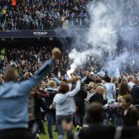 Photo - A flare is held up as Manchester City fans invade the pitch at the end of the English Premier League soccer match between Manchester City and West Ham at the Etihad Stadium in Manchester, England, Sunday May 11, 2014.  Manchester City won the Premier League for the second time in three seasons on Sunday, completing its campaign with a comfortable 2-0 victory over West Ham that lacked any of the drama of its previous title.  (AP Photo/Jon Super)