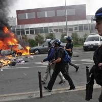 Photo - Riot police officers walk in the street of Sarcelles, during clashes with rioters, following a pro-Palestinian demonstration, in Sarcelles, north of Paris, Sunday, July 20, 2014.  French youth defying a ban on a protest against Israel's Gaza offensive went on a rampage in a Paris suburb, setting fire to cars and garbage cans after a peaceful demonstration. (AP Photo/Thibault Camus)