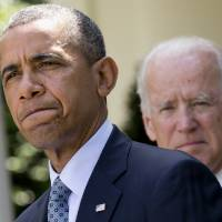 Photo - President Barack Obama, accompanied by Vice President Joe Biden, pauses while making an announcement about immigration reform, Monday, June 30, 2014, in the Rose Garden of the White House in Washington. The president said he's done waiting for House Republicans to act on immigration. He says he now plans to act on his own. Obama announced his intention Monday to take executive action.  (AP Photo/Jacquelyn Martin)