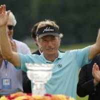 Photo - Bernhard Langer of Munich, Germany acknowledges the gallery after winning the  Senior Players Championship golf tournament at Fox Chapel Golf Club in Pittsburgh, Sunday, June 29, 2014. Langer defeated Jeff Sluman in the second hole of a playoff to win the tournament. (AP Photo/Gene J. Puskar)