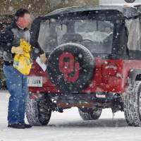 Photo - Larry Wright with Wright's IGA Supermarket prepares his four-wheel-drive vehicle to make home grocery deliveries as new snow falls on top of Tuesday's crippling winter storm accumulation on Friday, February 4, 2011, in Norman, Okla. Photo by Steve Sisney, The Oklahoman