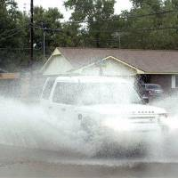 Photo - A car drives through a flooded street in Norman, Okla, Wednesday, Sept 8, 2010 after remnants of Tropical Storm Hermine brought heavy rains to the area. (AP Photo/The Norman Transcript, Kyle Phillips)