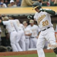 Photo - Oakland Athletics' Josh Donaldson scores after hitting a 2 run home run against San Francisco Giants starting pitcher Madison Bumgarner during the fourth inning of a baseball game in Oakland, Calif., Monday, May 27, 2013. (AP Photo/Tony Avelar)