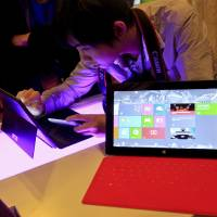 Photo -   FILE - In this Tuesday Oct. 23, 2012, file photo, a Chinese man tries out the new Surface tablet computer made by Microsoft at a show in Shanghai ahead of the launch of the operating system on Oct. 26. With the release of Windows 8, PC makers are doing their best to blur the boundaries between the PC and tablet with an array of devices that mash keyboards and touch screens together in different ways. (AP Photo) CHINA OUT