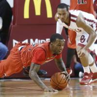 Photo - Texas Tech guard Jamal Williams, Jr. dives for a loose ball in front of Oklahoma guard Jordan Woodard during the first half on an NCAA college basketball game in Norman, Okla., Wednesday, Feb. 12, 2014. (AP Photo/Sue Ogrocki)