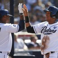 Photo - San Diego Padres' Yangervis Solarte high fives with Chris Nelson after scoring in the first inning of a baseball game against the Colorado Rockies Wednesday, Aug. 13, 2014, in San Diego. (AP Photo/Lenny Ignelzi)