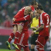 Photo - Bayern's Arjen Robben of the Netherlands lifts Bayern's Rafinha of Brazil to celebrate after scoring during the German first division Bundesliga soccer match between Bayern Munich and Eintracht Frankfurt in Munich, Germany, Sunday, Feb. 2, 2014. (AP Photo/Frank Augstein)