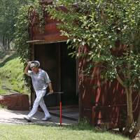 Photo - Gene Sauers walks out of an old railroad box car that serves as a bridge during the third round of play at the 2014 U.S. Senior Open golf tournament at Oak Tree National in Edmond, Okla., Saturday, July 12, 2014. Sauers finished the day as the leader. (AP Photo/Sue Ogrocki)