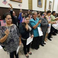 Photo -  Naturalized U.S. citizens Martha Cadena, left, and Leticia Gonzalez wave flags during a naturalization ceremony at the Oklahoma City federal courthouse on Friday. Photo by Paul Hellstern, The Oklahoman   PAUL HELLSTERN -  Oklahoman