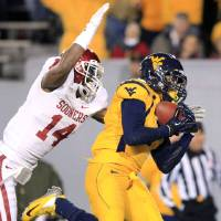 Photo -   West Virginia's Stedman Bailey (3) catches a pass for a touchdown as Oklahoma's Aaron Colvin (14) attempts to tackle during their NCAA college football game in Morgantown, W.Va., on Saturday, Nov. 17, 2012. (AP Photo/Christopher Jackson)