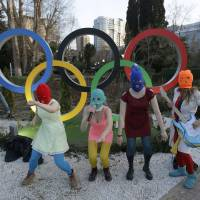 Photo - Members of the punk group Pussy Riot, including Nadezhda Tolokonnikova in the aqua balaclava, center, and Maria Alekhina in the red balaclava, left, perform next to the Olympic rings in Sochi, Russia, on Wednesday, Feb. 19, 2014. Cossack militia attacked the punk group with horsewhips earlier in the day as the artists - who have feuded with Vladmir Putin's government for years - tried to perform under a sign advertising the Sochi Olympics. (AP Photo/David Goldman)