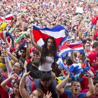 Photo - Costa Rica soccer fans celebrate a goal against Greece as they watch the World Cup round of 16 match on TV set up in a public square in San Jose, Costa Rica, Sunday, June 29, 2014. (AP Photo/Esteban Felix)