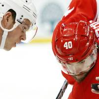 Photo - Chicago Blackhawks center Jonathan Toews, left, and Detroit Red Wings left wing Henrik Zetterberg (40), of Sweden, eye the puck on a face off in the second period of an NHL hockey game Wednesday, Jan. 22, 2014, in Detroit. (AP Photo/Paul Sancya)