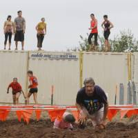 Photo - Participants negotiate the final obstacle of the Juggernaut mud run at Edmond's J.L. Mitch Park. The event raised money for Susan G. Komen for the Cure. PHOTO BY PAUL HELLSTERN, THE OKLAHOMAN  PAUL HELLSTERN
