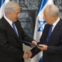 Photo - Israeli Prime Minister Benjamin Netanyahu, left, receives a folder from Israeli President Simon Peres in a brief ceremony in the president's Jerusalem residence Saturday, Feb. 2, 2013.  Israel's president has asked Netanyahu to form the next government, and Netanyahu says he wants to advance peace talks with the Palestinians. (AP Photo/Jim Hollander, Pool)