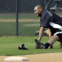 Photo - New York Yankees shortstop Derek Jeter stretches during practice at the Yankees' minor league facility Wednesday, Feb. 12, 2014, in Tampa, Fla.  Jeter says he will retire after this season. Jeter posted a long letter on his Facebook account Wednesday, Feb. 12, 2014,  saying the 2014 will be his last year playing professional baseball.(AP Photo/Chris O'Meara)